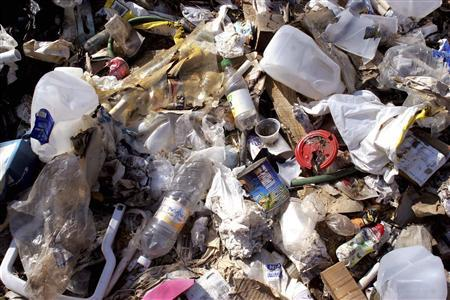 Trash awaits collection during a community trash collection event along the Santa Cruz River in Rio Rico